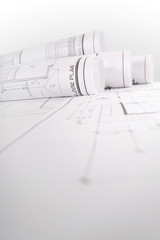 Monochrome image of rolled up blueprints