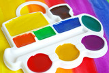 Box of watercolors and a brush on a colorful  background poster