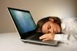 a woman sleeps on a laptop