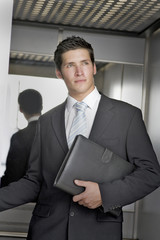 Sharp suited high flying young business man in an elevator