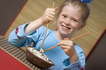 Little girl in blue eating rice with chopsticks