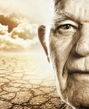 Elderly man's face over dry desert land background