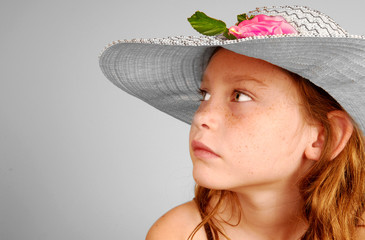 Young girl in fancy hat looking away