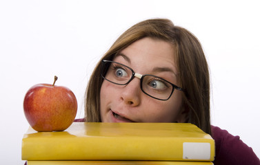 Close-up view of nerdy female student looking at apple.