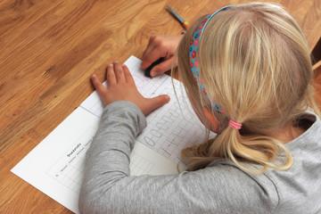 Young first grade girl doing her homework