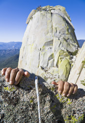 Rock climbers hands gripping the edge of a cliff.