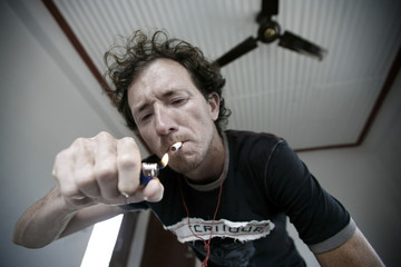 Young man lighting up a cigarette in hotel room