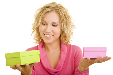 Junge Frau mit rosa Pullover vergleicht lachend zwei Geschenke