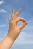 Human hand making OK sign against blue sky poster