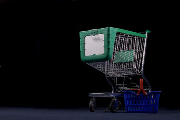 Big shopping cart and small basket in dark