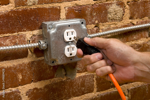 a man's hand plugging in an extension cord
