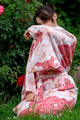 Girl in a pink yukata near rosebush.