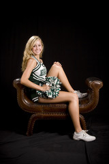 beautiful blond cheerleader seated in uniform