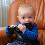 Adorable baby boy chewing the TV remote control - 9894472