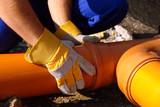Closeup of plumber's hands assembling pvc sewage pipes
