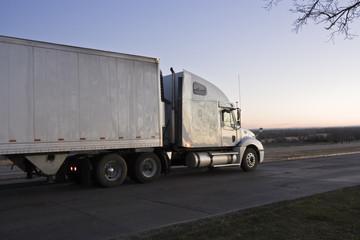 Sunrise drive - semi-truck on the road.