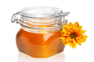 Honey jar, closed,with a chrysanthemum flower on it, isolated