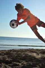 Boy playing football on beach, close up