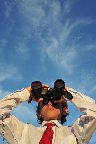 Young business man looking through binocular, low angle view