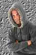 Young man fashion with a hood isolated in grey