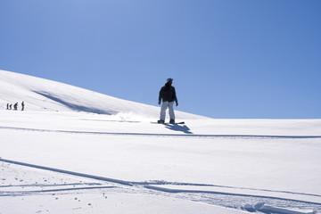 Snowboarder in clean untouched snow slope with copy space