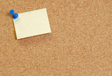 cork board with blank note attached with thumb pin.. poster