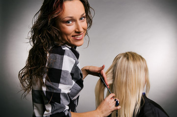 smiley hairdresser with client. studio shot over grey background