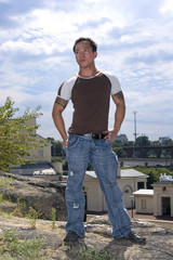 handsome muscular asian man standing on hill