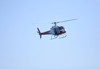 TV-news helicopter in flight with a cameraman shooting
