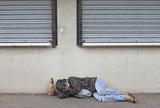 Homeless man asleep on the sidewalk poster