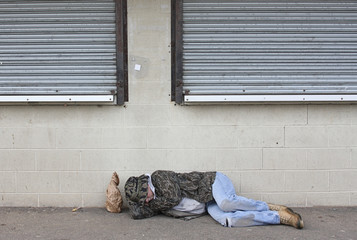 Homeless man asleep on the sidewalk