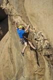 Climber scaling an overhanging rock face. poster