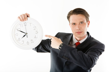 Portrait of serious businessman with clock pointing at it