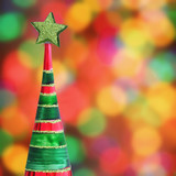 Christmas tree ornament on defocused Christmas lights poster