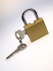 closed padlock with inserted keys on  light background