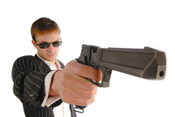 man in  black suit with a pistol in  hand, close up