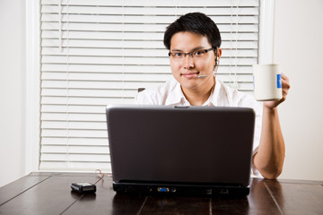 An asian entrepreneur working on his laptop from home