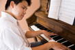 A shot of an asian man playing piano