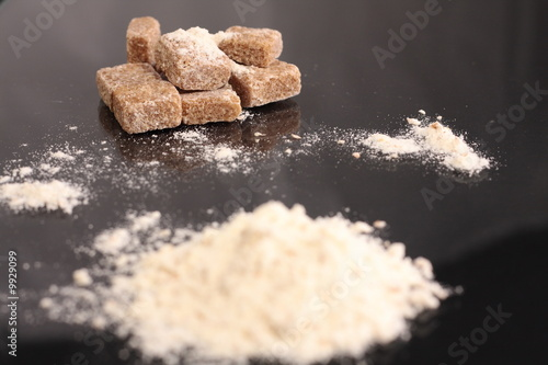 Brown sugar cubes and flour on black surface