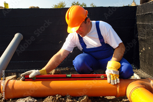 Plumber measuring slope of assembled sewage pipes