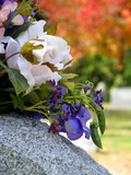 silk flowers on a cemetery grave headstone poster