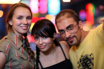 Three friends posing in night city. Shallow DOF.
