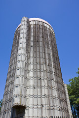 An old grain silo from the ground shot toward the blue sky