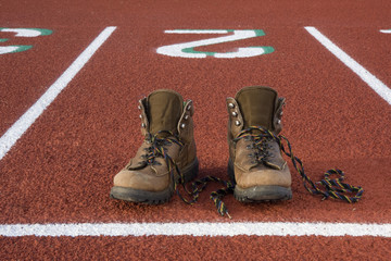 heavy hiking boots at starting line on a running track,