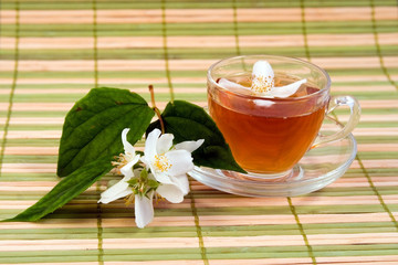 Transparent teacup with tea and flower