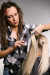 professional hairdresser doing haircut over grey background