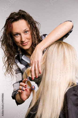 smiley hairdresser working with client