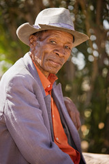 Portrait of elderly  african man with a broken had and old suit