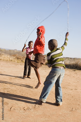 Fotobehang Overige african children jumping rope in the sand,