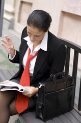 attractive young businesswoman reading magazine
